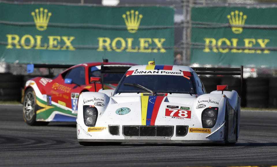 Photo - Brendan Hartley (78), of New Zealand, drives the Dinan/Riley through a turn and passes Matt Griffin, of Ireland, in the Spirit of Race Ferrari 458 Italia, during the IMSA Series Rolex 24 hour auto race at Daytona International Speedway in Daytona Beach, Fla., Saturday, Jan. 25, 2014.(AP Photo/John Raoux)