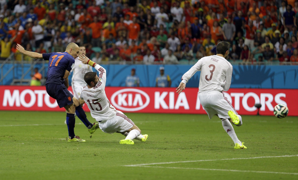 Photo - FILE - In this June 13, 2014 file photo, Netherlands' Arjen Robben kicks past Spain's Sergio Ramos (15) and Gerard Pique to score his side's second goal during the second half of the group B World Cup soccer match at the Arena Ponte Nova in Salvador, Brazil. Robben had already scored one goal in the rout over Spain, but his second was done with awe-inspiring speed. (AP Photo/Natacha Pisarenko, File)