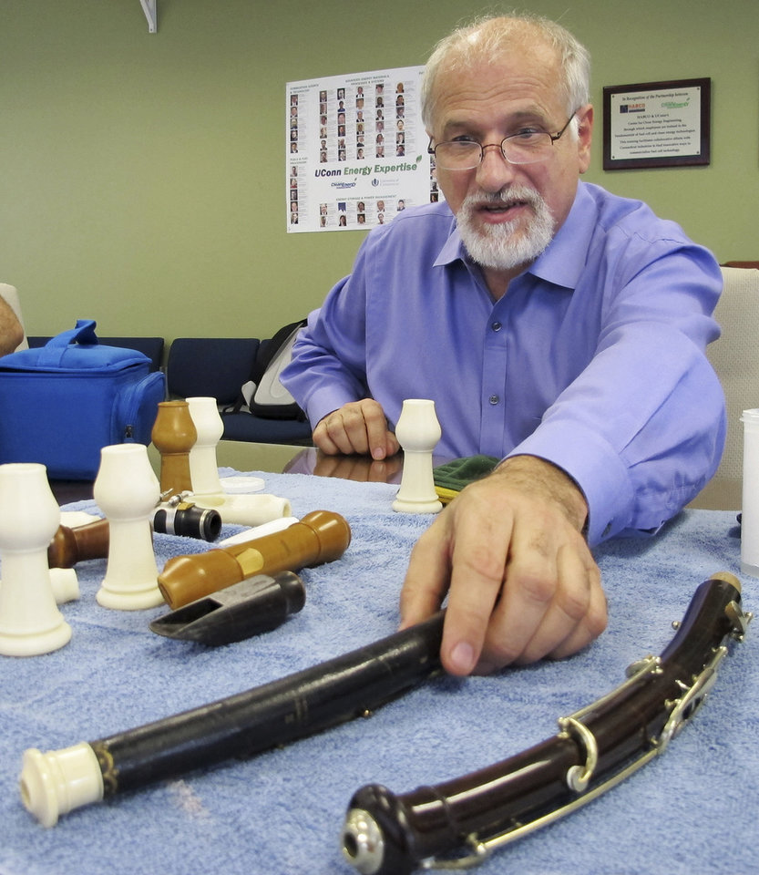 Photo - In this July 17, 2014 photo, Dr. Robert Howe, a medical doctor and a PhD candidate in music history, displays antique English horns at the University of Connecticut's Depot Campus in Mansfield, Conn. Howe and his colleagues have been using CT scans and 3D printing to unlock the secrets of antique instruments and make replica parts that will allow them to be played. (AP Photo/Pat Eaton-Robb)