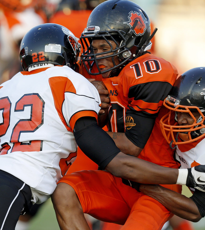 Photo - Brandon Gaddis of Douglass is brought down by Booker T. Washington's Raymond Ratliff, left, and Kevin Dorsey during their high school football game at Douglass in Oklahoma City, Friday, September 6, 2013. Photo by Bryan Terry, The Oklahoman