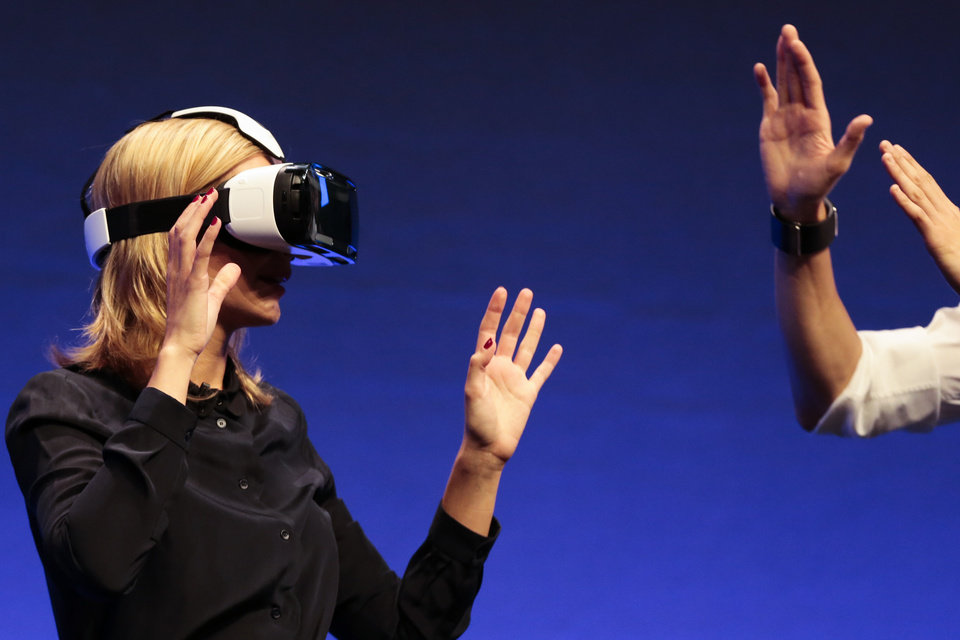 Photo - English television presenter Rachel Riley shows a virtual-reality headset called Gear VR,  during an unpacked event of Samsung ahead oh the consumer electronic fair IFA in Berlin, Wednesday, Sept. 3, 2014. (AP Photo/Markus Schreiber)