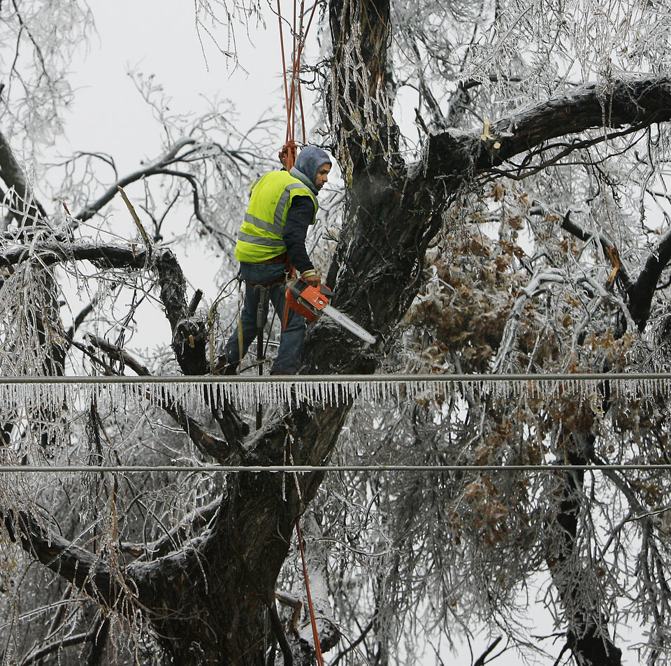 WINTER / COLD / WEATHER / ICE STORM: Isaac Mujica is suspended by a rope about 30 feet above the ground as he uses a chainsaw to cut ice-covered branches away from power lines along Interstate 40 near SE 15 Street in Del City Monday afternoon, Dec. 10, 2007. By Jim Beckel, The Oklahoman. ORG XMIT: KOD