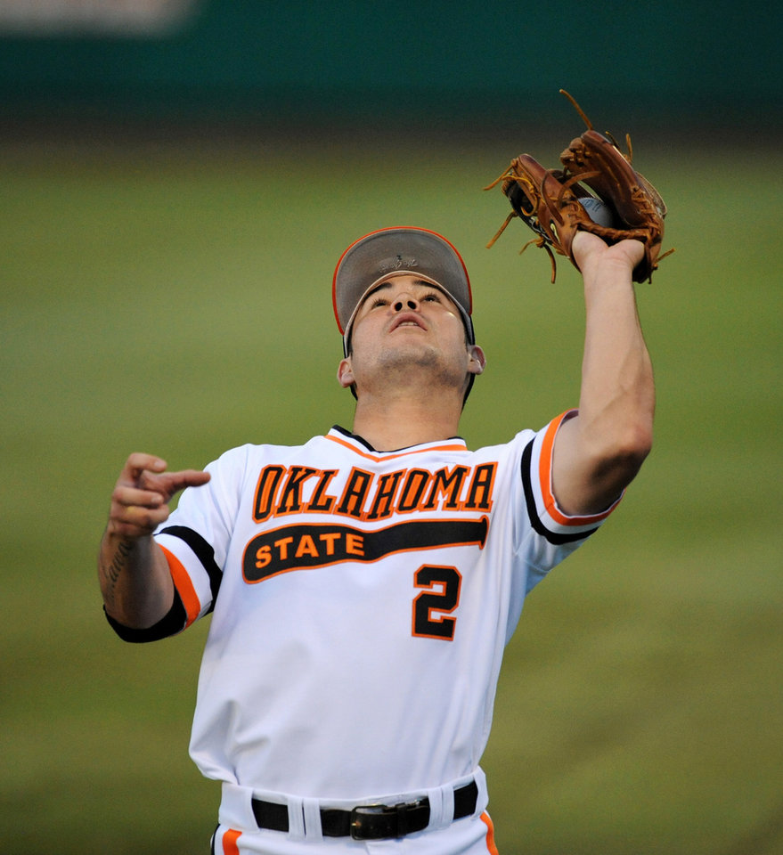 Photo - Oklahoma State infielder Tim Arakawa catches a fly ball for an out during the first inning of an NCAA college baseball super regional tournament game in Stillwater, Okla, Friday, June 6, 2014. (AP Photo/Brody Schmidt)