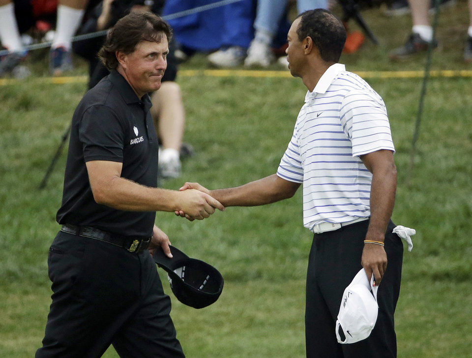 Photo - Phil Mickelson, left, shakes Tiger Wood's hand after the second round of the PGA Championship golf tournament at Valhalla Golf Club on Friday, Aug. 8, 2014, in Louisville, Ky. (AP Photo/David J. Phillip)