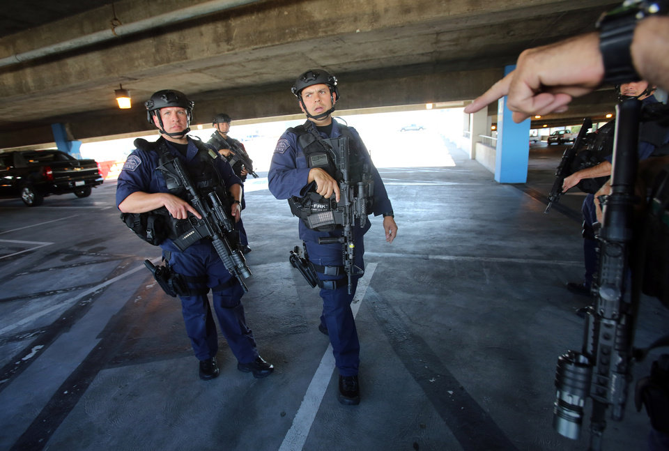 Photo - SWAT officers search a parking structure during a security check at Los Angeles International Airport on Friday Nov. 1, 2013. A gunman armed with a semi-automatic rifle opened fire at the airport on Friday, killing a Transportation Security Administration employee and wounding two other people. (AP Photo/Ringo H.W. Chiu)