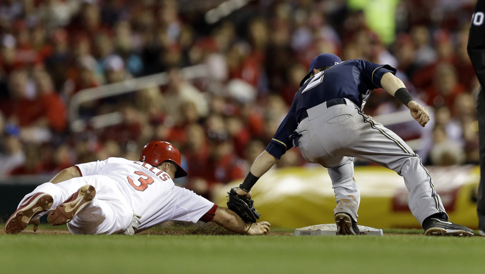Photo - St. Louis Cardinals' Mark Ellis, left, is tagged out by Milwaukee Brewers second baseman Scooter Gennett while trying to get back to first base during the during the fifth inning of a baseball game Monday, April 28, 2014, in St. Louis. Brewers first baseman Mark Reynolds was covering an attempted bunt on the play. (AP Photo/Jeff Roberson)