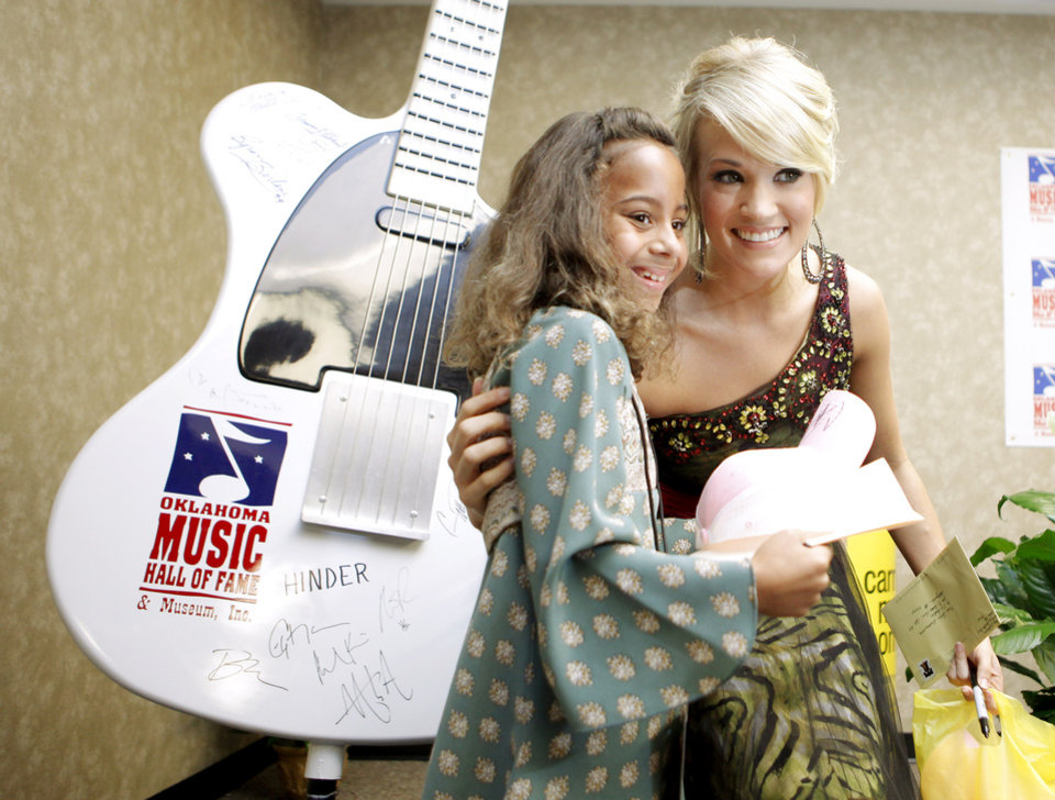 Photo - INDUCT / INDUCTED / INDUCTION / INDUCTEE: Carrie Underwood poses for a photo with Kiarra Smith, 10, from Okmulgee, Okla., after a press conference for her induction into Oklahoma Music Hall of Fame in Muskogee, Okla., Thursday, September 17, 2009. Photo by Bryan Terry, The Oklahoman ORG XMIT: KOD