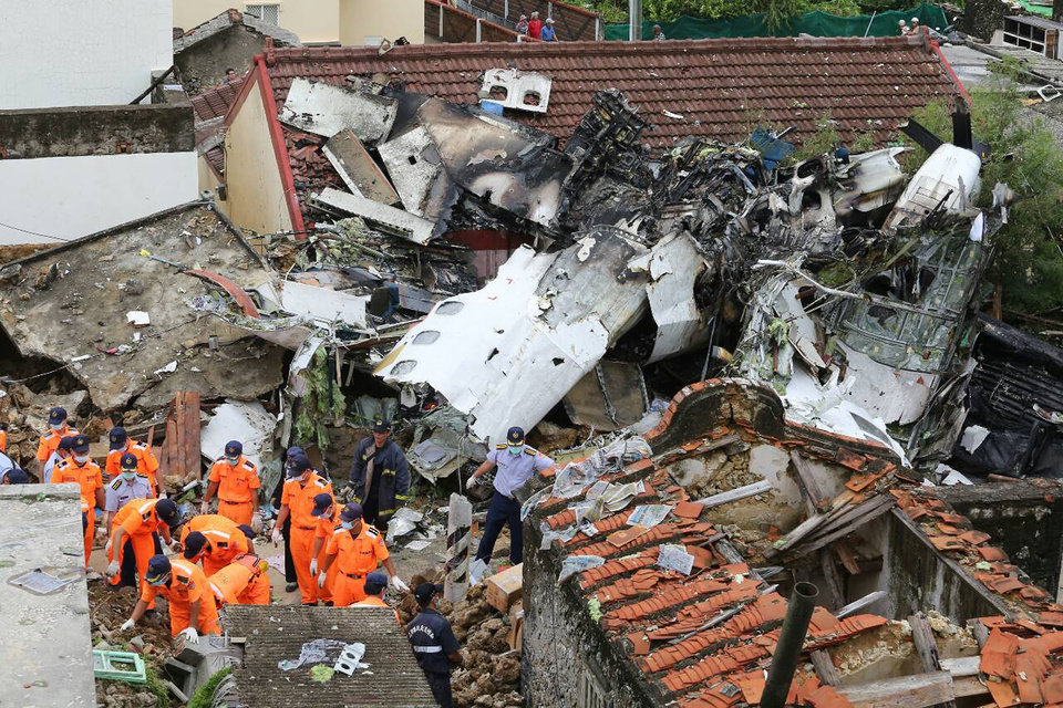 Photo - Rescue workers survey the wreckage of TransAsia Airways Flight GE222 which crashed on the Taiwanese island of Penghu Thursday, July 24, 2014. The plane attempting to land in stormy weather crashed on the island late Wednesday, killing more than 40 people and wrecking houses and cars on the ground. (AP Photo) TAIWAN OUT