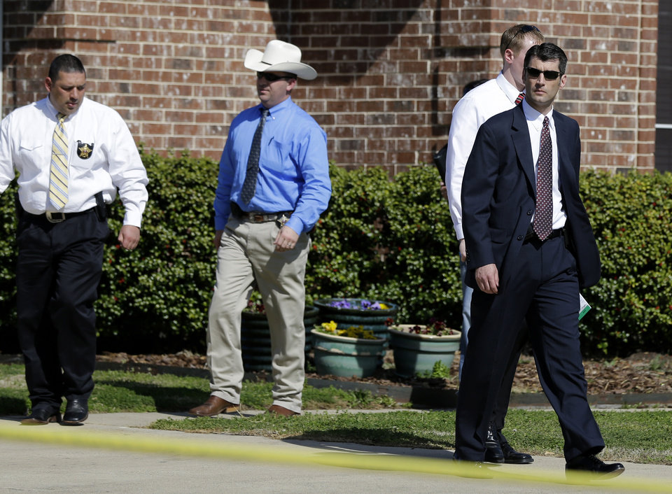 Photo - Law enforcement officials walk out of the home of Kaufman District Attorney Mike McLelland Monday, April 1, 2013, near Forney, Texas. McLelland and his wife were murdered on Saturday at their home. (AP Photo/Tony Gutierrez)