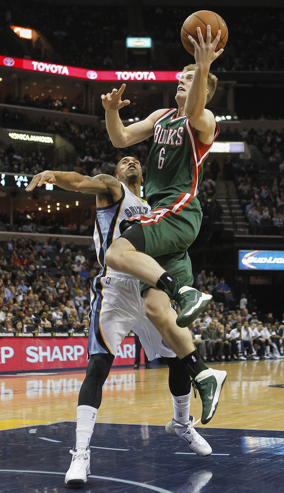 Photo - Milwaukee Bucks guard Nate Wolters (6) goes to the basket against Memphis Grizzlies forward Courtney Lee in the first half of an NBA basketball game on Saturday, Feb. 1, 2014, in Memphis, Tenn. (AP Photo/Lance Murphey)