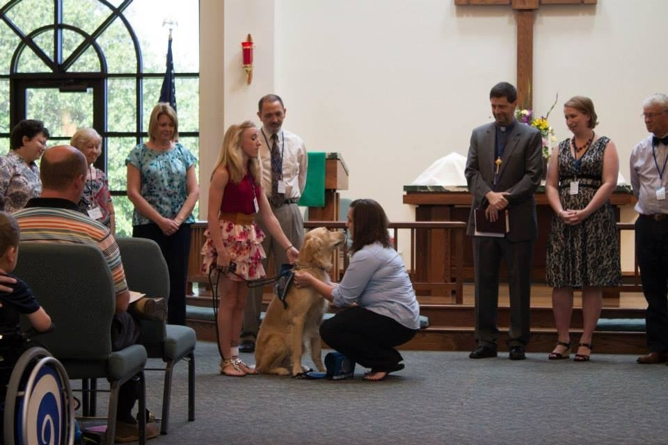 Photo -  Hannah McGinnis, 19, of Maywood, Ill., helps as Sherry Bolosan with Addison, Ill.-based Lutheran Church Charities, places a Comfort Dog vest on Rufus Comfort Dog during a Passing of the Leash ceremony at St. Mark Lutheran Church in Edmond. Photo by Mandy Long, for The Oklahoman