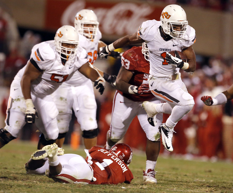 Oklahoma State\'s Joseph Randle (1) leaps over Oklahoma\'s Tony Jefferson (1) during the Bedlam college football game between the University of Oklahoma Sooners (OU) and the Oklahoma State University Cowboys (OSU) at Gaylord Family-Oklahoma Memorial Stadium in Norman, Okla., Saturday, Nov. 24, 2012. OU won 51-48 in overtime. Photo by Sarah Phipps, The Oklahoman
