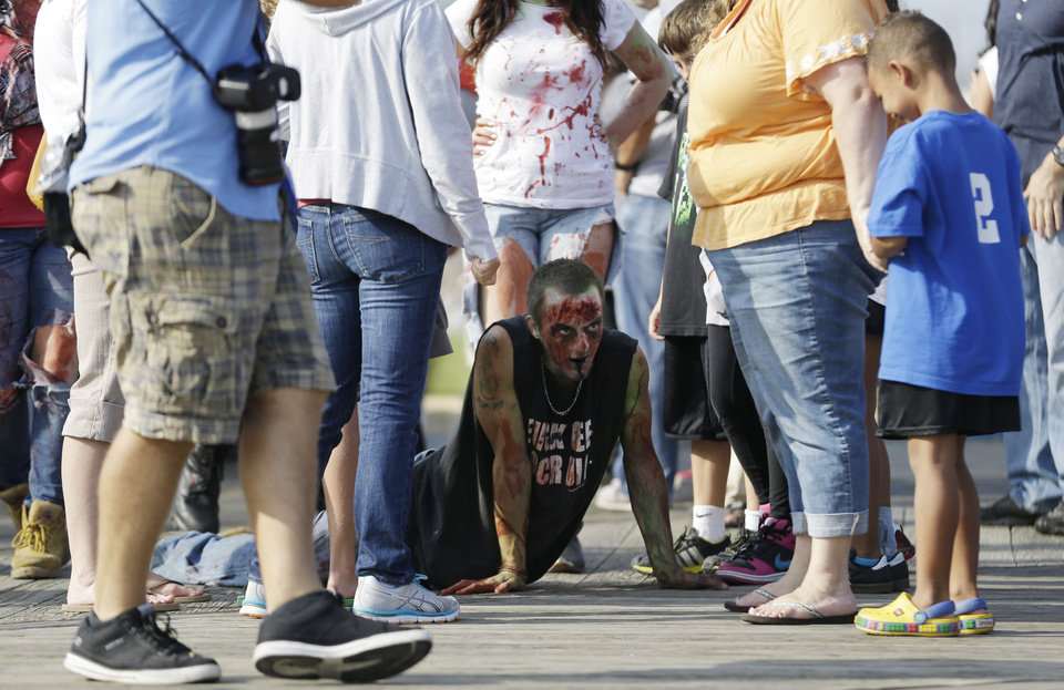Photo - Joe Wiley, center, of Hamilton, N.J., crawls on the Asbury Park boardwalk during a zombie walk, Saturday, Oct. 5, 2013, in Asbury Park, N.J. According to Guinness World Record adjudicator Michael Empric, the 9,592 zombies gathered sets a new record for largest zombie walk. (AP Photo/Julio Cortez) ORG XMIT: NJJC116