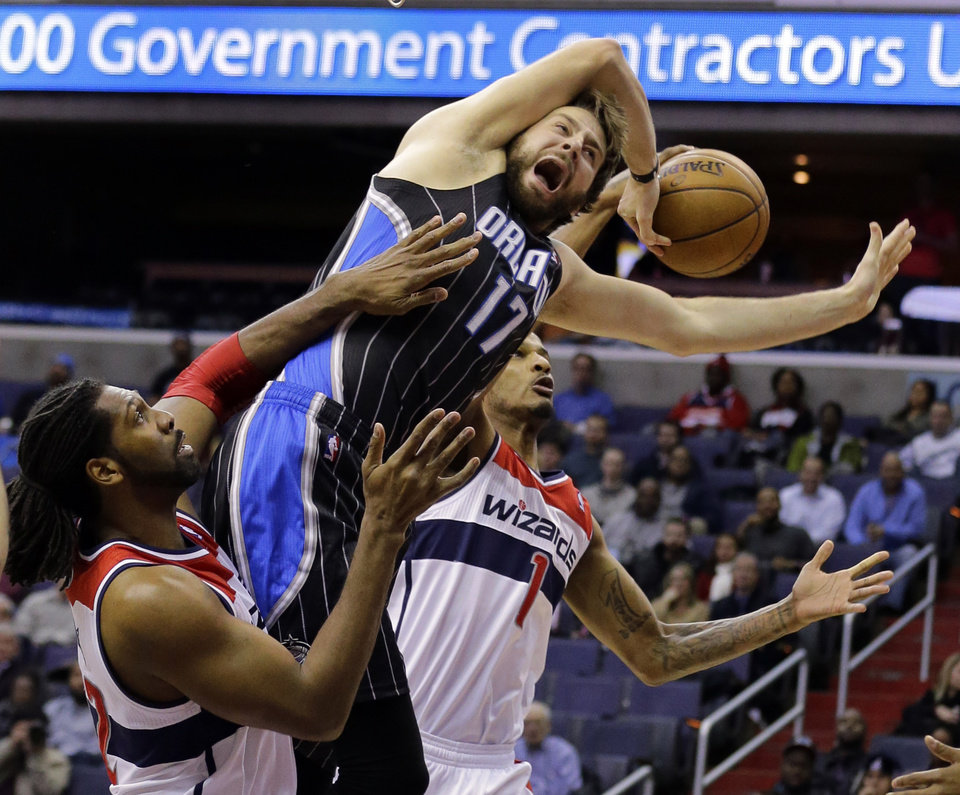 Orlando Magic forward Josh McRoberts (17) has the ball stripped by Washington Wizards forward Trevor Ariza (1) as he runs into center Nene (42) from Brazil, in the first half of an NBA basketball game Monday, Jan. 14, 2013 in Washington. (AP Photo/Alex Brandon)