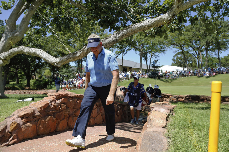 Photo - Colin Montgomerie walks to the fifth tee during the second round of the U.S. Senior Open golf tournament at Oak Tree National in Edmond, Okla., Friday, July 11, 2014. (AP Photo/Sue Ogrocki)
