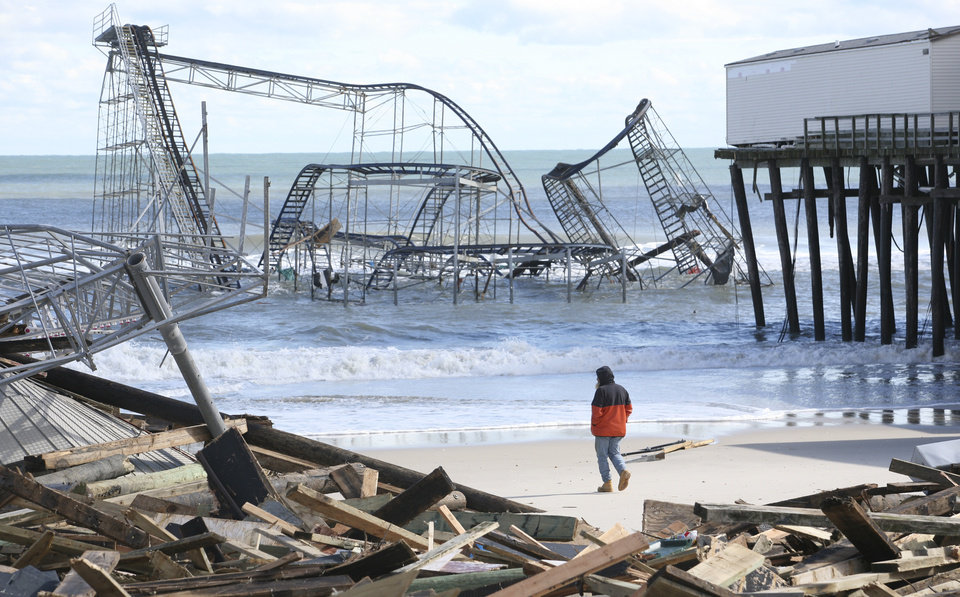 Photo -   A man looks over the debris on the Seaside Heights, N.J., beach near Casino Pier on Wednesday, Oct. 31, 2012. (AP Photo/Star-Ledger, David Gard/POOL)