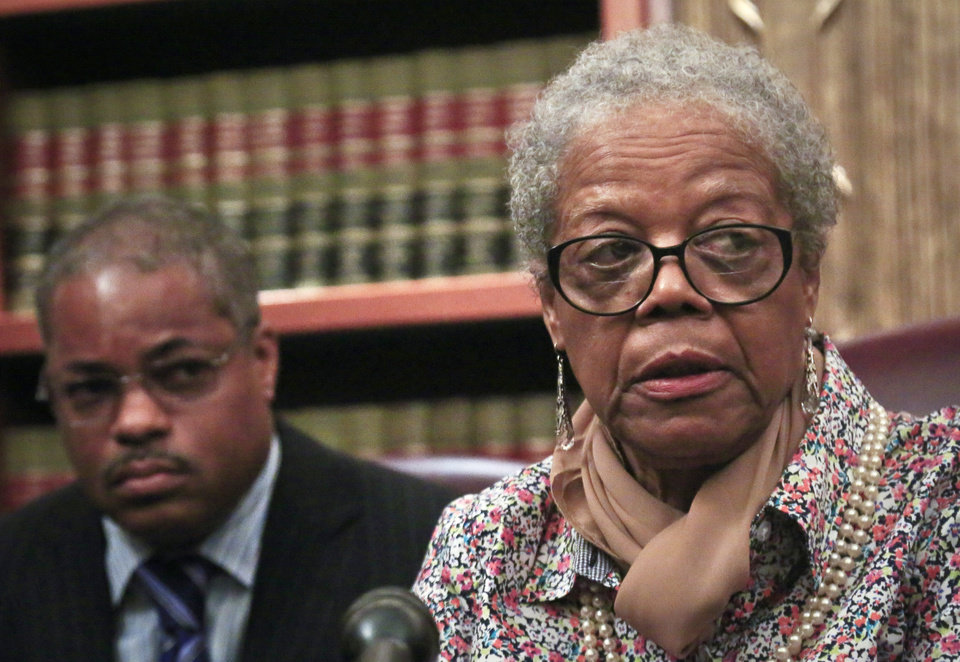 Photo - Attorney Derek Sells, left, listens as Alma Murdough speaks during a press conference on Friday May 16, 2014 in New York. Sells plans to file a $25 million wrongful death lawsuit against the city on behalf of Alma Murdough for the death of her son, Marine Jerome Murdough, who was found dead in a 100 degree cell on Rikers Island.  (AP Photo/Bebeto Matthews)