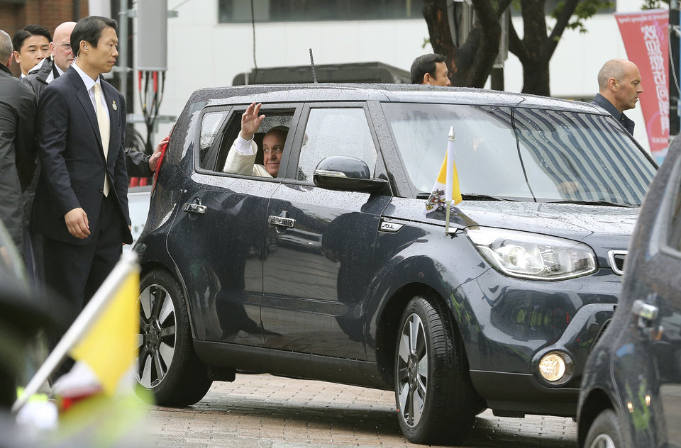 Photo - Pope Francis waves from a car after celebrating a Mass for peace and reconciliation outside Myeong-dong cathedral in Seoul, South Korea, Monday, Aug. 18, 2014. Pope Francis wrapped up his first trip to Asia on Monday by challenging Koreans - from the North and the South - to reject the