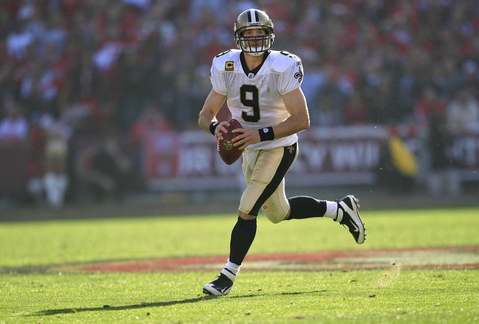 Photo -   FILE - In this Jan. 14, 2012, file photo, New Orleans Saints quarterback Drew Brees rolls out to pass against the San Francisco 49ers during the second quarter of an NFL divisional playoff football game in San Francisco. Brees has agreed to a five-year, $100 million contract with the Saints, with $60 million guaranteed, on Friday, July 13, 2012, a person familiar with the deal tells The Associated Press. (AP Photo/Marcio Jose Sanchez, File)