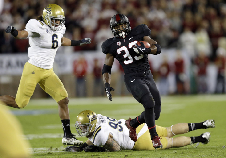 Photo - Stanford running back Stepfan Taylor (33) carries past UCLA defensive end Cassius Marsh (99) and linebacker Eric Kendricks (6) during the second half of the Pac-12 championship NCAA college football game in Stanford, Calif., Friday, Nov. 30, 2012. (AP Photo/Marcio Jose Sanchez)