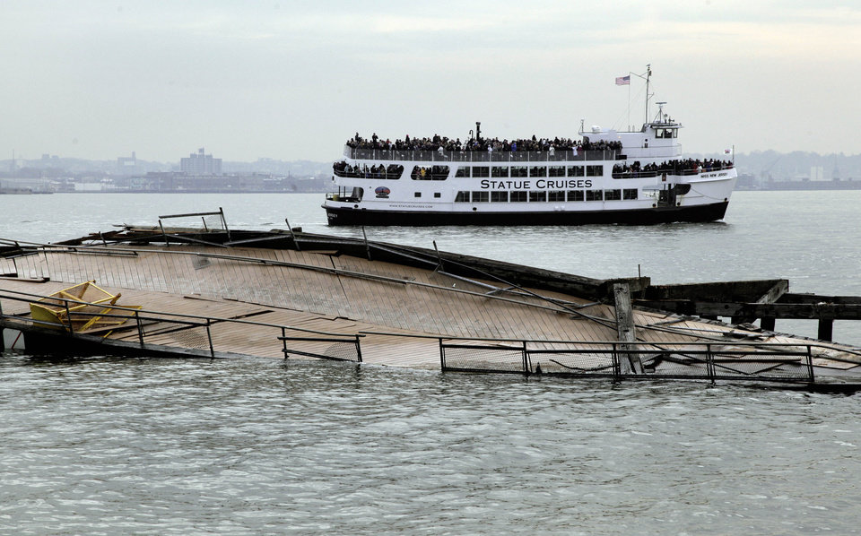 Photo - A Statue Cruises tour boat passes the damaged auxiliary pier on Liberty Island, in New York, Friday, Nov. 30, 2012. Tourists in New York will miss out for a while on one of the hallmarks of a visit to New York, seeing the Statue of Liberty up close. Though the statue itself survived Superstorm Sandy intact, damage to buildings and Liberty Island's power and heating systems means the island will remain closed for now, and authorities don't have an estimate on when it will reopen. (AP Photo/Richard Drew)