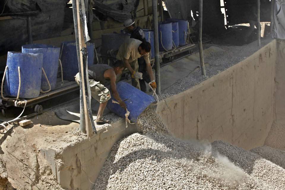 Photo - Palestinian workers unload gravel being pulled from a smuggling tunnel along the border between the Gaza Strip and Egypt, in Rafah, southern Gaza Strip, Wednesday, July 24, 2013. Egypt has sealed smuggling tunnels and blocked most passenger traffic in the toughest border restrictions on the Gaza Strip in recent years, causing millions of dollars in economic losses and prompting concerns among Gaza's Hamas rulers that the territory is being swept up in the Egyptian military's crackdown on Islamic fundamentalists. (AP Photo/Adel Hana)