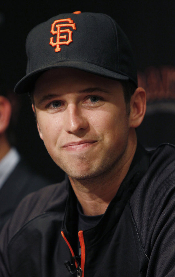San Francisco Giants\' Buster Posey smiles during a news conference, Friday, March 29, 2013, in San Francisco. Posey and the Giants have agreed to a $167 million, nine-year contract, a deal that includes a club option for 2022 that could raise the value to $186 million over a decade.(AP Photo/George Nikitin)