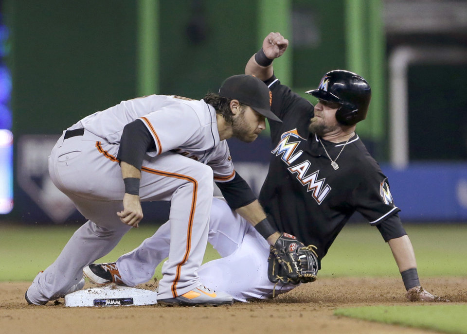 Photo - Miami Marlins' Casey McGehee steals second base as San Francisco Giants shortstop Brandon Crawford is unable to tag him out in time during the first inning of a baseball game, Saturday, July 19, 2014, in Miami. (AP Photo/Wilfredo Lee)