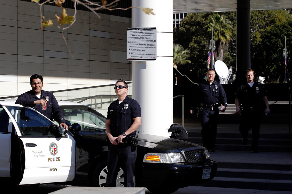 Photo - Los Angeles police officers stand alert at the LAPD headquarters in Los Angeles on Tuesday, Feb. 12, 2013. Police are now investigating more than 1,000 tips from the public in the search for the Christopher Dorner, who is suspected of a deadly revenge plot against the Los Angeles Police Department.  The number of tips has grown from an initial 250 since the city offered a $1 million reward for information leading to the capture of Dorner. (AP Photo/Nick Ut)