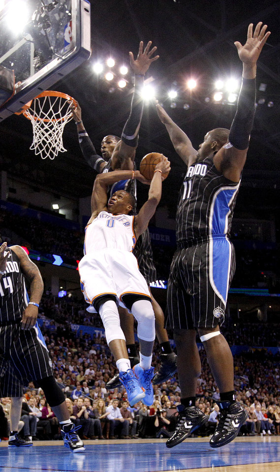 Oklahoma City Thunder's Russell Westbrook (0) tries to shoot in between Dwight Howard (12) and Glen Davis (11) during the opening day NBA basketball game between the Oklahoma CIty Thunder and the Orlando Magic at Chesapeake Energy Arena in Oklahoma City, Sunday, Dec. 25, 2011. Photo by Sarah Phipps, The Oklahoman
