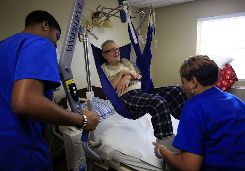 Karen Moralez, right, and Kevin Mobley help Bob Matthews into bed at an Oklahoma City rehabilitation center Tuesday. Matthews contracted West Nile virus this past summer and is working to recover. Recovering from West Nile virus can be a slow and painful process. Photo by Sarah Phipps, The Oklahoman <strong>SARAH PHIPPS</strong>