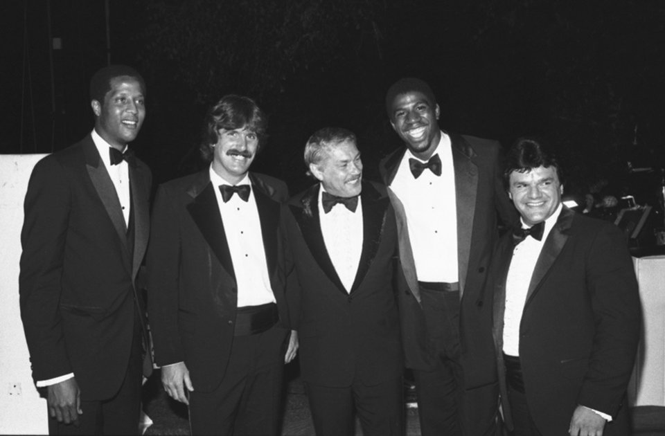 FILE - In this June 18, 1980 file photo, Jerry Buss, center, poses with players from his teams at a charity event in Beverly Hills, Calif. From left are Los Angeles Lakers' Jamaal Wilkes, Los Angeles Kings' Charlie Simmer, Buss, Lakers' Magic Johnson and Kings' Marcel Dionne. Buss, the Lakers' playboy owner who shepherded the NBA franchise to 10 championships, has died. He was 79. Bob Steiner, an assistant to Buss, confirmed Monday, Feb. 18, 2013  that Buss had died in Los Angeles. Further details were not available. (AP Photo/Reed Saxon, File)