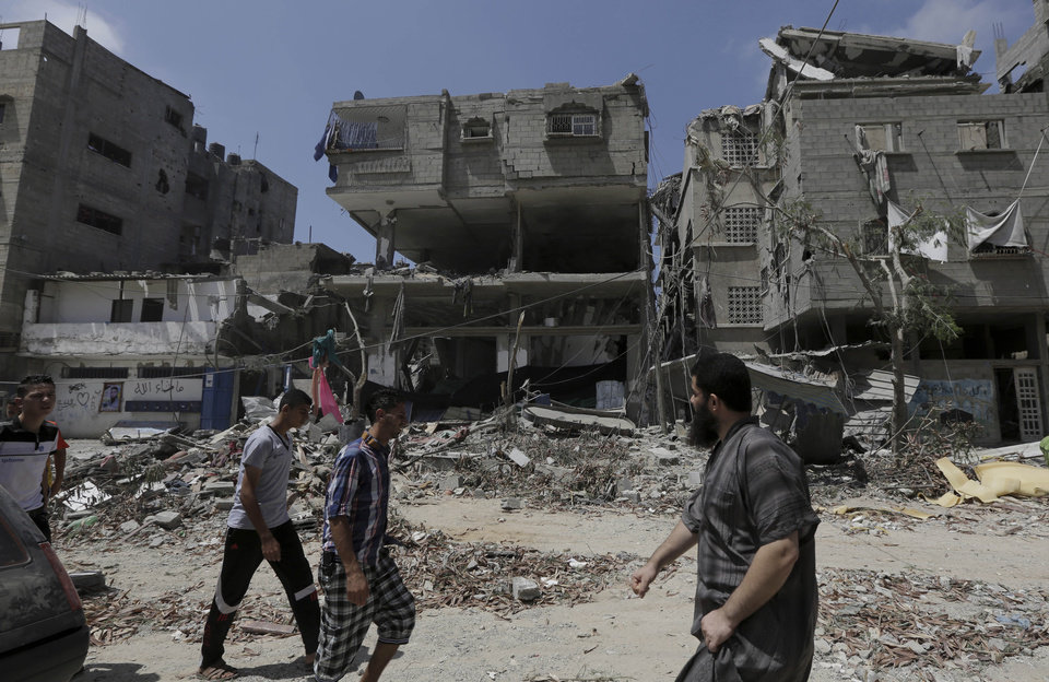 Photo - Palestinians pass by the rubble of damaged buildings after an Israeli strike in Gaza City in the northern Gaza Strip, Sunday, Aug. 24, 2014. (AP Photo/Adel Hana)