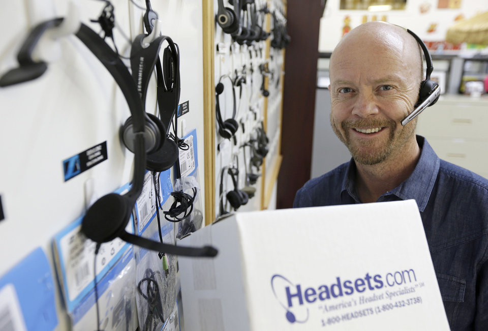 In this Tuesday, Jan. 15, 2013, photo, CEO and President Mike Faith of Headsets.com poses by a display of headsets in his offices in San Francisco. Headsets.com, might have to hire two staffers to handle the administrative work if what's called remote tax collection becomes law, says Faith. The company has operations in California and Tennessee, but sells to all 50 states. Currently, federal law only requires the company to collect tax in those two states. (AP Photo/Eric Risberg)