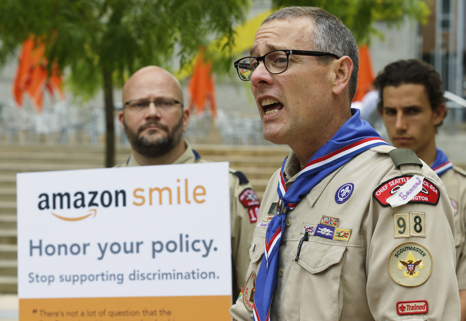 Photo - Geoffrey McGrath, right, a gay Boy Scout troop leader and Eagle Scout from Seattle, who had his membership in the Scouts revoked by the organization earlier this year, speaks in front of a group of Boy Scouts and scout leaders, Wednesday, May 21, 2014, outside the headquarters of Amazon.com in Seattle. The group delivered a petition bearing more than 125,000 signatures, urging Amazon to stop donating money to the Boy Scouts due to the organization's policy of excluding openly gay adults from leadership positions, despite recently accepting gay youth as scouts. (AP Photo/Ted S. Warren)