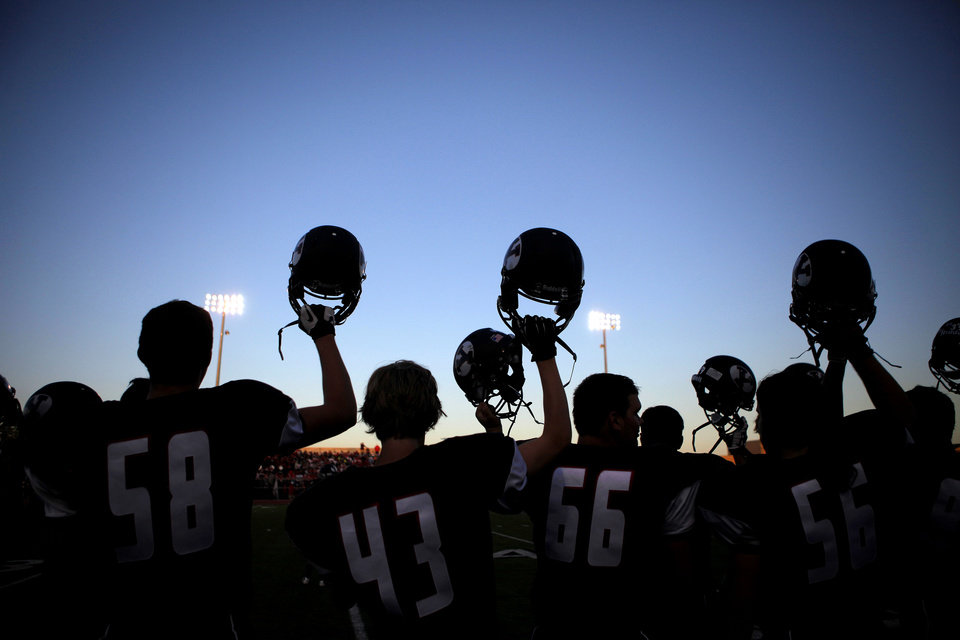 Photo - Yukon football players raise their helmets during a high school football game against Mustang in Yukon, Okla., Friday, August 31, 2012. Photo by Bryan Terry, The Oklahoman