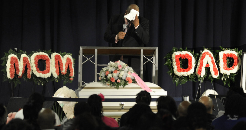 Photo - Rev. Corey Brooks wipes his face while speaking during six-month old Jonylah Watkins' funeral at New Beginnings Church in Chicago, Tuesday, March, 19, 2013.  Jonylah's death was the latest to draw national attention to Chicago's struggle with gang violence and murder.  (AP Photo/Paul Beaty)