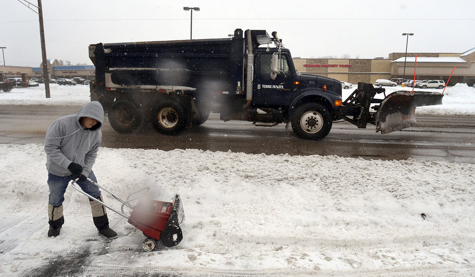 In this Dec. 26, 2012 photo, USA Nails manager David Ngo of Terre Haute, Ind., tries to start his snow blower as a city snow plow drives by in Terre Haute, Ind. (AP Photo/The Tribune-Star, Joseph C. Garza)