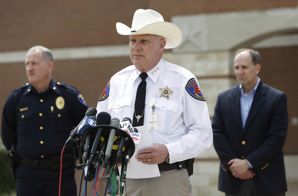 Photo - Kaufman County Sheriff David Byrnes, center, speaks at a news conference, Sunday, March 31, 2013, in Kaufman, Texas. On Saturday, Kaufman County District Attorney Mike McLelland and his wife, Cynthia, were murdered in their home. (AP Photo/Mike Fuentes)