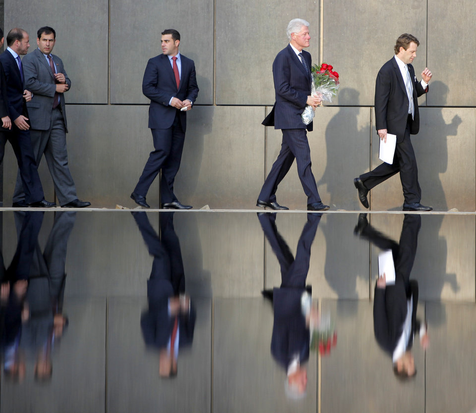 Photo - Former President Bill Clinton carries flowers as he visits the Oklahoma City National Memorial in Oklahoma City, Wednesday, April 21, 2010. Clinton is in town to receive the Reflections of Hope Award for his work in Oklahoma City after the bombing of the Alfred P. Murrah Federal Building.  Photo by Bryan Terry, The Oklahoman