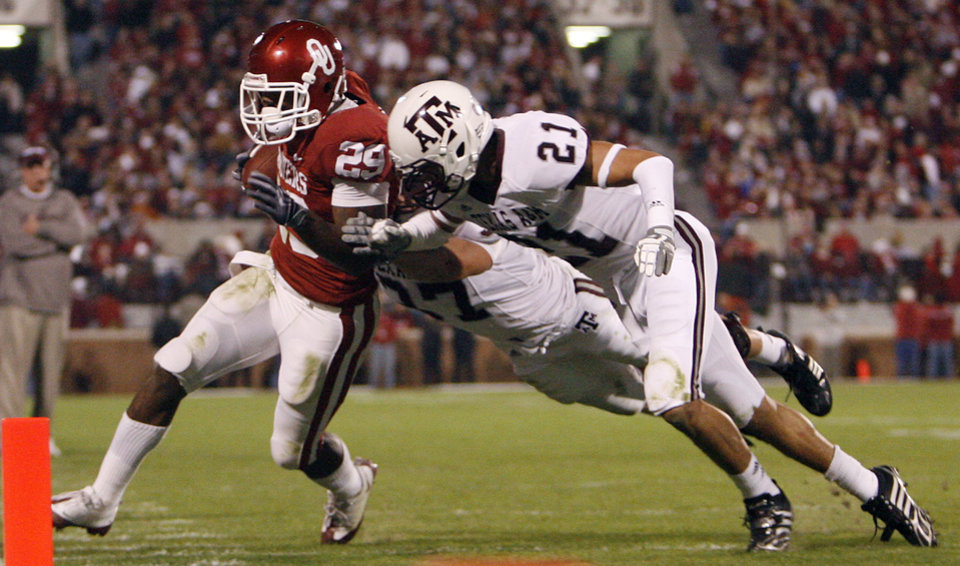 Photo - Oklahoma's Chris Brown (29) is forced out of bounds by Texas A&M's Justin McQueen (21) during the first half of the college football game between the University of Oklahoma Sooners (OU) and the Texas A&M Aggies at Gaylord Family-Memorial Stadium on Saturday, Nov. 14, 2009, in Norman, Okla. 