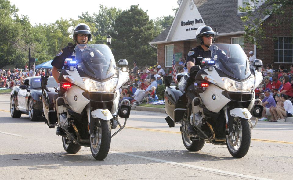 Photo - The Edmond Police Dept. leads the annual LibertyFest Fourth of July Parade in downtown Edmond, OK, Thursday, July 4, 2013,  Photo by Paul Hellstern, The Oklahoman