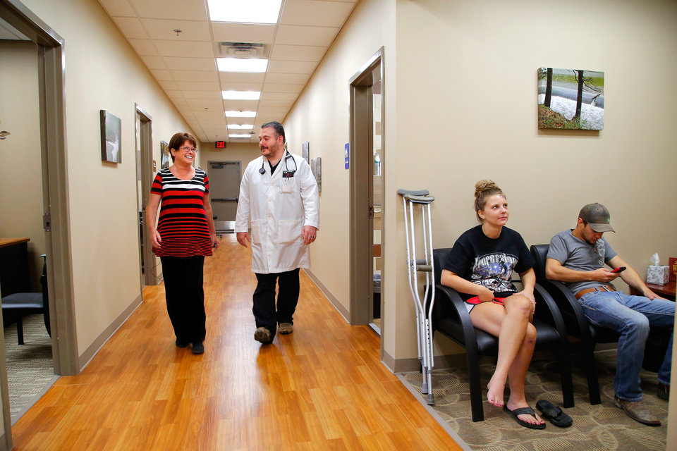 Photo -  Angie Batton, CEO for the new Pushmataha Family Medical Center in Clayton, talks with nurse practitioner Nathan Harper as they walk past the X-ray room in the spacious clinic. President Barack Obama designated five areas of the U.S. as Promise Zones, and the Choctaw Nation was one of those. Photo by Jim Beckel, The Oklahoman