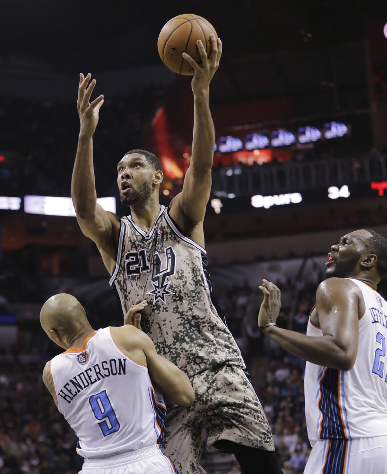 Photo - San Antonio Spurs' Tim Duncan (21) shoots over Charlotte Bobcats' Gerald Henderson (9) and Al Jefferson, right, during the first half of an NBA basketball game, Friday, Feb. 28, 2014, in San Antonio. (AP Photo/Eric Gay)