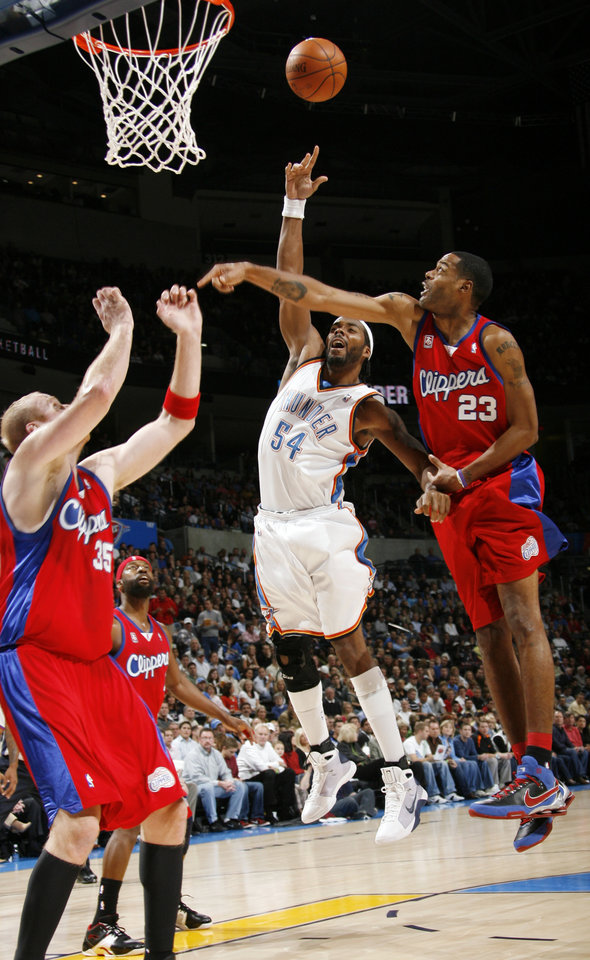 Photo - Chris Wilcox of the Thunder shoots past, from left, Chris Kaman, Baron Davis and Marcus Camby of the Clippers in the first half of the NBA basketball game between the Oklahoma City Thunder and the Los Angeles Clippers at the Ford Center in Oklahoma City, Wednesday, Nov. 19, 2008. BY NATE BILLINGS, THE OKLAHOMAN