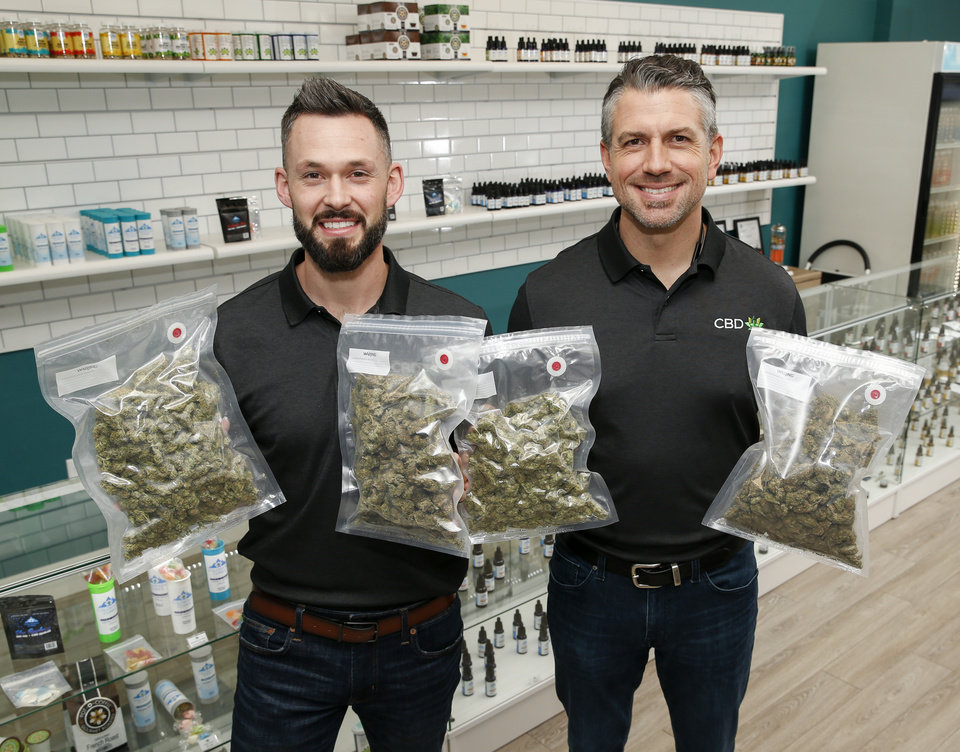 Photo -  CBD Plus USA Executive Vice President Jake Chilcoat, left, and CBD Plus USA President Matt Baker hold one-pound bags of cannabis flowers on Monday in Oklahoma City. [Photo by Nate Billings, The Oklahoman]