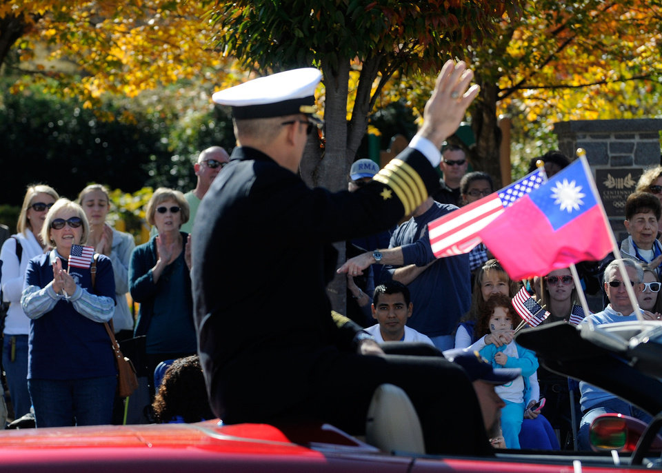 Crowds wave to Navy Capt. Jim Minta as he participates in the 31st annual Veterans Day Parade in downtown Atlanta, Saturday, Nov. 10, 2012. (AP Photo/David Tulis)