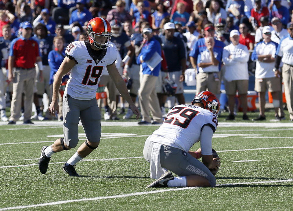 Photo - Oklahoma State's Ben Grogan (19) kicks an extra point as Zach Sinor (29) holds in the second quarter during the college football game between the Oklahoma State Cowboys (OSU) and the Kansas Jayhawks at Memorial Stadium in Lawrence, Kan., Saturday, Oct. 22, 2016.   Photo by Sarah Phipps, The Oklahoman