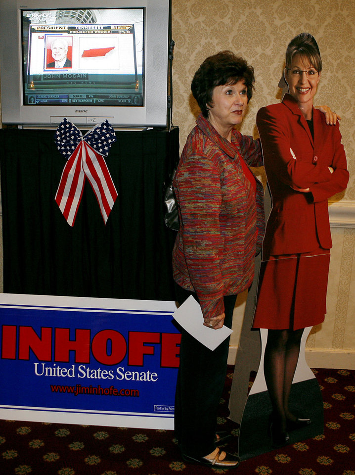 Photo - Suzanne Vaughn, of Edmond, Okla., poses with a cardboard cutout of Sarah Palin, as election results come in over the television during the Republican watch party at the Oklahoma City Marriott on Northwest Expressway in oklahoma City on Tuesday Nov. 4, 2008. By John Clanton, The Oklahoman