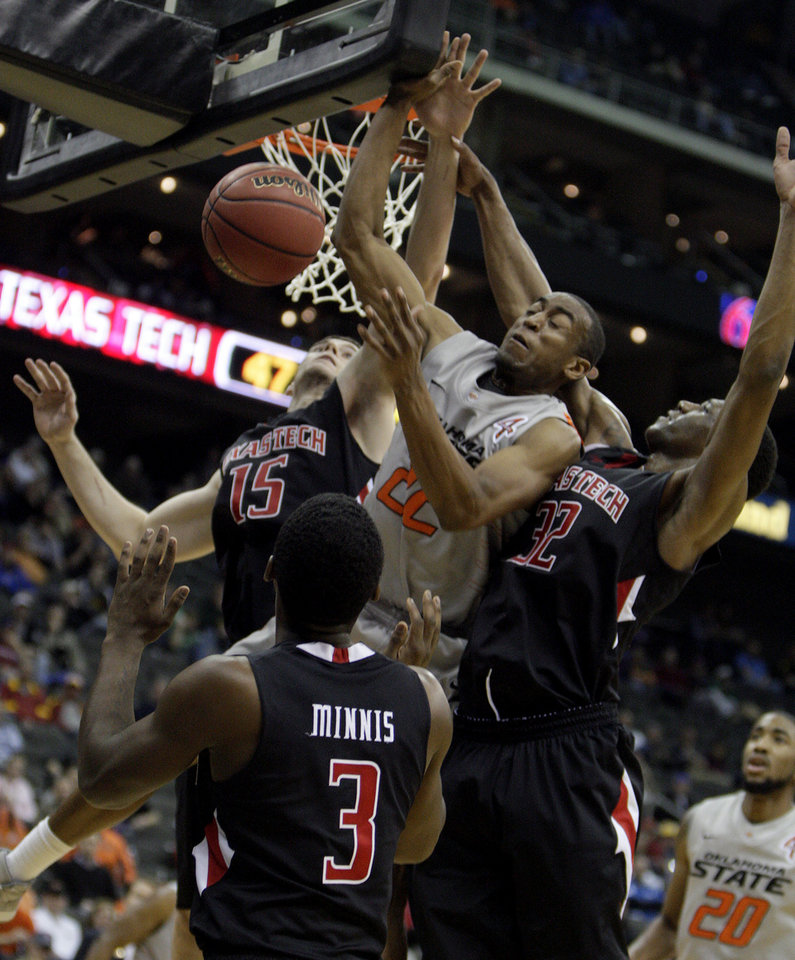Photo - Oklahoma State's Markel Brown (22) fights for a rebound with Texas Tech's DeShon Minnis (3), Robert Lewandowski (15) and Jordan Tolbert (32) during the Big 12 tournament men's basketball game between the Oklahoma State Cowboys and the Texas Tech Red Raiders at the Sprint Center, Wednesday, March, 7, 2012. Photo by Sarah Phipps, The Oklahoman